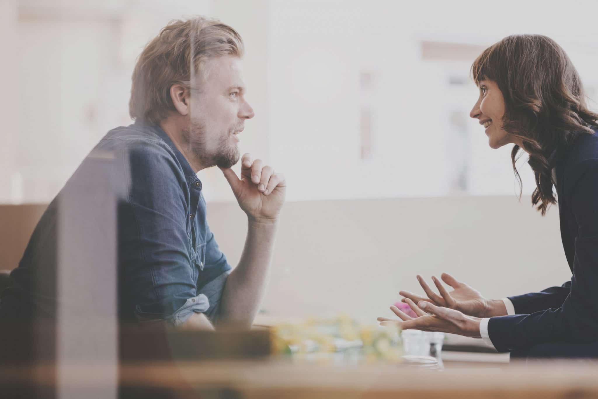 Zwei Business Personen, eine Frau und ein Mann, sitzten sich gegenüber und reden.